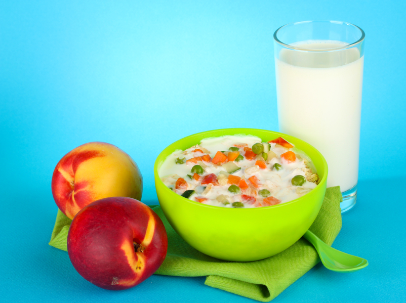 tasty dieting food, fruits and glass of milk, on blue background